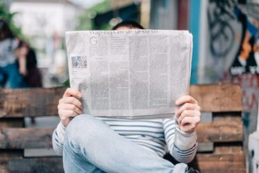 Person Reading How the News Media Makes Money
